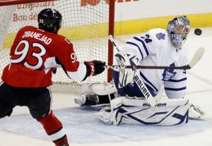 Ottawa Senators' Mika Zibanejad knocks the puck out of the air to score against Toronto Maple Leafs' goalie James Reimer during their pre-season NHL game in Ottawa